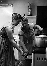 Staff Member and Catherine working at the wood stove in the Madonna House kitchen.