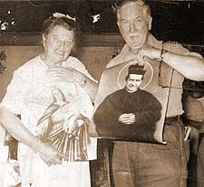 Catherine and Eddie Doherty holding paintings of Our Lady with Jesus and Don Bosco.